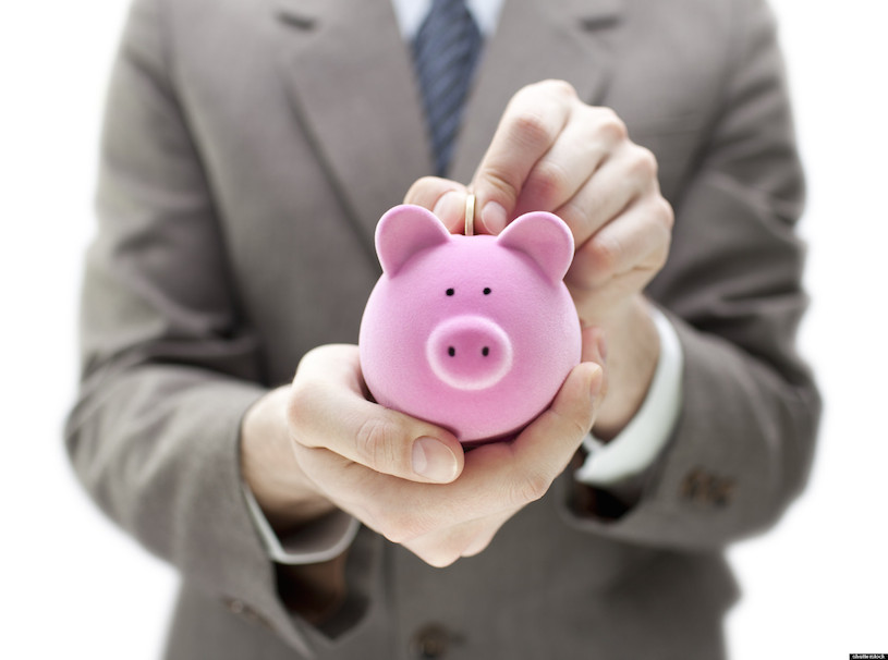Businessman putting coin into the piggy bank; Shutterstock ID 76160650; PO: The Huffington Post; Job: The Huffington Post; Client: The Huffington Post; Other: The Huffington Post
